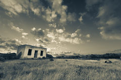 Old small deserted house in field with cloud sunset landscape ar Stock Image