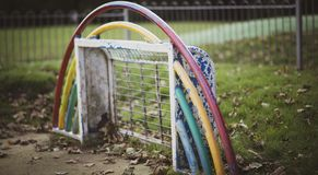 An abandoned painted childrens football goal in a playground with peeling paint
