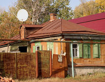 Old small house with big TV dish. Old poor small house with big satellite TV dish shot in central russia Stock Photo