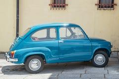 Old, small, Italian car: fiat 600 in perfect condition. Yellow background. Old, small, Italian car: fiat 600 in perfect condition. Yellow wall as background stock photo
