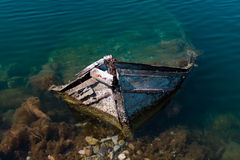 Old Small Mediterranean Fishing Boat Sinking inside the Pier of Nea Artaki in Euboea - Nea Artaki, Greece. A small Port in Nea Artaki, Euboea - Nea Artaki Stock Photo