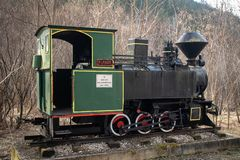 Old small steam locomotive on part of railway in the forest like a monument and tourist attraction stock image