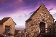 Old small stone houses at Rasnov medieval citadel from Transylvania. In sunset light stock image