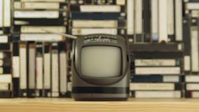 Old small TV against video tapes background. Camera moving away, dolly shot. Old small TV set with antenna against background made of VHS and S-VHS video tapes stock video