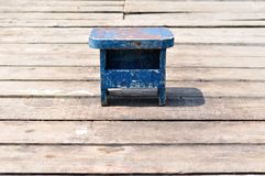 Old small wooden blue fishing chair on wooden fishing pier Stock Image
