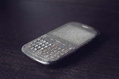 Old smartphone with dust on black shelf Royalty Free Stock Images