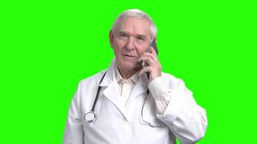 Old smiling doctor talking on the phone. Portrait of old doctor using smartphone in green hroma background stock video