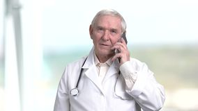 Old smiling doctor talking on phone. Senior therapist having converstation on phone, bright abstract blurred background stock footage