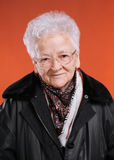 Old smiling woman. In glasses on orange background stock photography