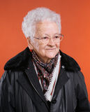 Old smiling woman. In glasses on orange background royalty free stock photos