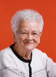 Old smiling woman. In glasses on orange background royalty free stock image