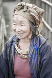 Old smiling woman in Arunachal Pradesh. Ziro, Arunachal Pradesh - circa March 2012: Old smiling woman in blue jacket and with brown headcloth poses in Ziro Royalty Free Stock Photo