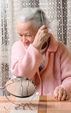 Old smiling woman combing her hair at home Stock Photo
