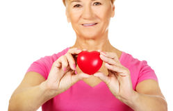 Old smiling woman holding red toy heart Royalty Free Stock Photography