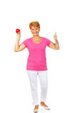 Old smiling woman holding red toy heart with thumb up Stock Photo