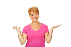 An old smiling woman presenting something.  Stock Images