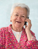 Old smiling woman talking on phone Stock Photography