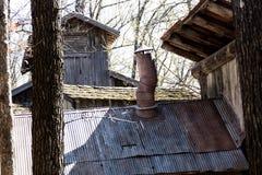 Old smoke crooked flue. Old smoke crooked chimney setting askew on tin roof on sunshiny day Royalty Free Stock Photos