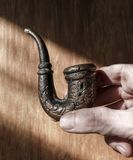 Old smoke pipe in male hand. Old smoke tobacco pipe in male hand on the scratched wooden background Stock Photos