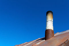 Old smoke pipe out of the rusty iron roof. In the background a clear blue sky Royalty Free Stock Image