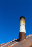 Old smoke pipe out of the rusty iron roof. In the background a clear blue sky Royalty Free Stock Images