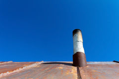 Old smoke pipe out of the rusty iron roof. In the background a clear blue sky Royalty Free Stock Photos