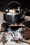 Old smoked metal pot on wooden fireplace while cooking indian tea.  Outdoor kitchen. Royalty Free Stock Image