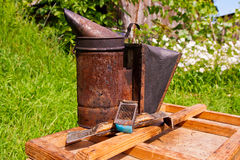 Old smoker and other tool of the beekeeper on the wooden box. Royalty Free Stock Photo