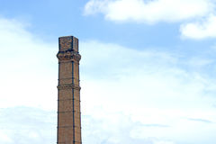 Old smokestack In the blue sky stock photo
