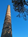 Old smokestack and blue sky and tree royalty free stock photo