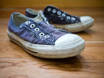 Old Sneakers. Shoes off - A favorite pair of old worn blue sneakers or trainers royalty free stock photography