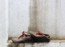 Old sneakers on the background wall. Royalty Free Stock Photo