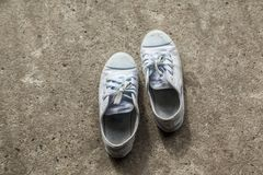 Old sneakers on basically the concrete. stock photo