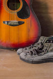 Old sneakers and guitar Stock Image