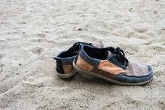 Old sneakers on the sand at the beach. Vintage background. Stock Photos