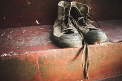 Old sneakers stand on red concrete Royalty Free Stock Photography
