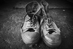 Old sneakers standing on concrete floor Royalty Free Stock Photo