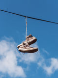 Old sneakers on a wire Stock Images