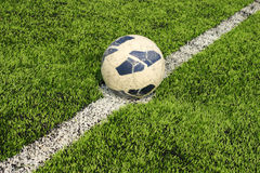 Old soccer ball on artificial turf Stock Photo