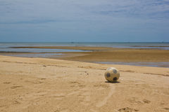 Old soccer ball on beach Stock Images