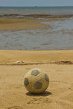 Old soccer ball on beach Royalty Free Stock Image