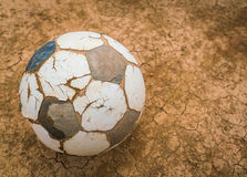Old soccer ball on Dry and cracked ground texture . Royalty Free Stock Image