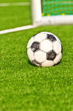Old soccer ball   football goals background. Old soccer ball on  football field with football goals background Stock Photo