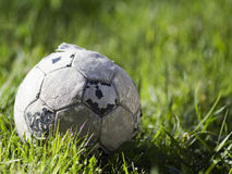 Old soccer ball on the grass Royalty Free Stock Image