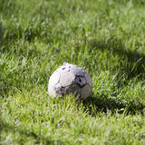 Old soccer ball on the grass Stock Photos