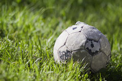 Old soccer ball on the grass Stock Image