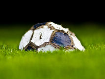 Old soccer ball on grass. Background, end of the game Stock Photography