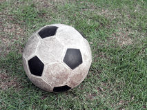 Close up old soccer ball made of synthetic rubber on green grass field. Old soccer ball made of synthetic rubber on green grass field, sport equipment for Royalty Free Stock Photos