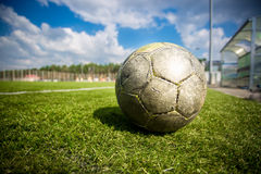 Old soccer ball on grass field at sunny day Royalty Free Stock Photography