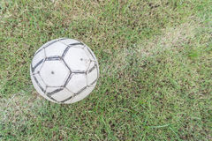 Old soccer ball on the grass of football field Royalty Free Stock Images